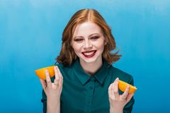 Beautiful smiling redhead girl photographed with fruit on a blue background. Royalty Free Stock Photography