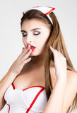 Beautiful smiling sexy nurse standing and wipes lipstick from lips Stock Photography