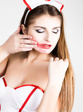 Beautiful smiling sexy nurse standing and wipes lipstick from lips Royalty Free Stock Photos