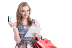 Beautiful smiling shopper holding tablet and card doing shopping. Beautiful smiling shopper holding tablet and credit or debit card doing shopping online Stock Photos