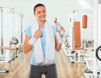 Beautiful smiling sportswoman holding bottle of water and lookin Stock Image