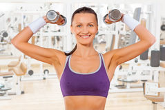 Beautiful smiling sportswoman holding two dumbbells Royalty Free Stock Photo