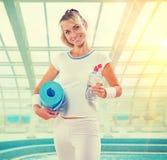 Beautiful smiling sportswoman holding yoga mat opened bottle wit Royalty Free Stock Images
