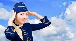 Beautiful  smiling stewardess on a background sky. Beautiful  smiling stewardess in uniform on a background sky Stock Photo