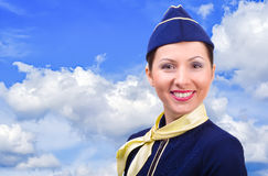 Beautiful smiling stewardess. On a background sky Stock Photography