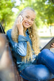 Beautiful smiling student with a phone in hand Stock Photo