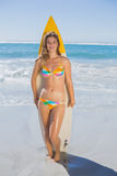 Beautiful smiling surfer girl standing on the beach with her surfboard Royalty Free Stock Image