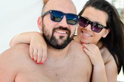 Happy  couple    on the beach. Beautiful smiling tanned bearded muscular men and smiling brunette  hugging on  the beach in luxury hotel Royalty Free Stock Image