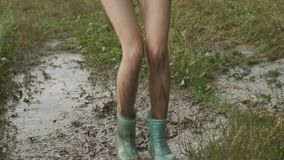 Beautiful smiling teen girl jumping in very muddy puddle on country road stock footage