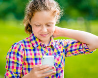 Beautiful smiling teenage girl in casual clothes with smartphone. In her hand, looking at screen, reading a message, using Facebook in sunny day in summer park stock photography