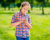 Beautiful smiling teenage girl in casual clothes with smartphone. In her hand, looking at screen, reading a message, using Facebook, texting and chatting stock photo