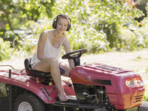 Beautiful smiling teenage girl cutting the lawn. Beautiful smiling teegage girl wearing ear muffs on a ride on mower cutting the lawn in a rural garden stock image