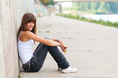 Beautiful smiling teenage girl sitting on the stre Stock Photo