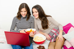 Beautiful smiling teenage girls watching movies on notebook. And eating cookies and popcorn on bed Royalty Free Stock Images