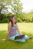 Beautiful smiling teenager with tablet pc, outdoors royalty free stock photography