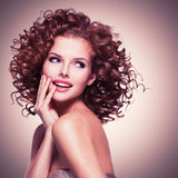 Beautiful smiling thoughtful woman with curly hair. stock photo