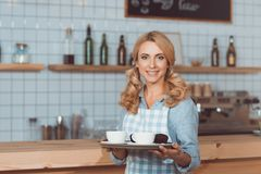Beautiful smiling waitress in apron holding tray with dessert and cups. Of coffee stock image