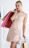 Beautiful smiling walking woman wearing dress holding colored pa stock photos