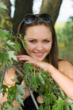 Beautiful smiling woman. Portrait of beautiful smiling woman behind the tree branch stock photos