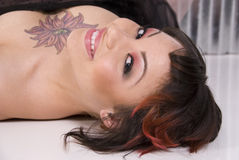 Beautiful smiling woman. Close up of a beautiful brunette with unusual tattoo laying on her back. Dramatic make up royalty free stock photo