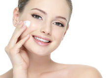 Beautiful smiling woman applying  cream on cheek. Beautiful face of young smiling woman applying cream on the cheek - white background Stock Image