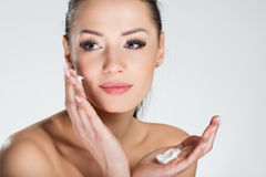 Beautiful smiling woman applying cream on face Stock Photography