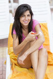 Beautiful smiling woman applying sun-protection cream Stock Photos