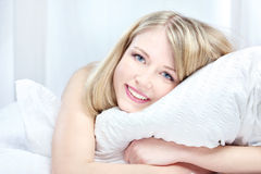 Beautiful smiling woman on bed at bedroom. Portrait of beautiful smiling woman on bed at bedroom royalty free stock image