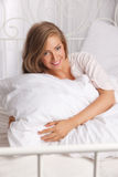 Beautiful smiling woman in the bed Royalty Free Stock Photo