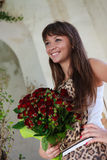 Beautiful smiling woman with a bouquet of red roses Royalty Free Stock Photography