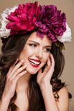 Beautiful smiling woman with bright flowers on her head. touching face Stock Photos