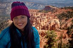 Beautiful smiling woman at Bryce Canyon in winter with blue coat and purple knit hat. Beautiful smiling woman standing at the rim of Bryce Canyon with a view of stock images