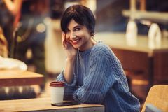 Beautiful smiling woman in the cafe with warm cozy interior and drinking coffee royalty free stock photos