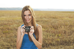 Beautiful smiling woman with camera on nature Royalty Free Stock Photos