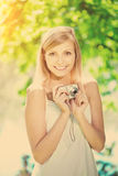 Beautiful smiling woman with a camera, outdoors Royalty Free Stock Image