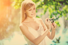 Beautiful smiling woman with a camera, outdoors Royalty Free Stock Images