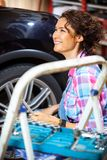 Beautiful smiling woman car mechanic. In blue overalls in the garage preparing the car for autotravel Stock Photography