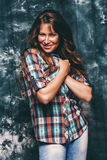Beautiful smiling woman in check shirt. In studio Royalty Free Stock Images