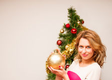 Beautiful  smiling woman and the Christmas tree. Royalty Free Stock Image
