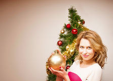 Beautiful  smiling woman and the Christmas tree. Stock Image