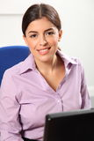 Beautiful smiling woman at computer in office Stock Image