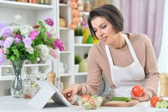 Portrait of a beautiful smiling woman cooking at kitchen stock photography