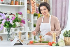 Portrait of beautiful smiling woman cooking at kitchen stock photography