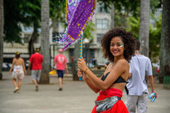 Beautiful smiling woman with curly hair and nose piercing, holding purple flag at Bloco Orquestra Voadora, Carnaval 2017 Royalty Free Stock Photos