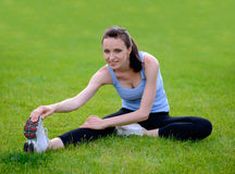 Beautiful Smiling Woman Doing Stretching Exercise on the Grass in the Park Royalty Free Stock Photography
