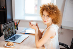 Beautiful smiling woman drinking coffee at table and using laptop Stock Image