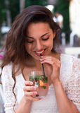 Beautiful smiling woman drinking cold lemonade berry, outdoor Royalty Free Stock Photography