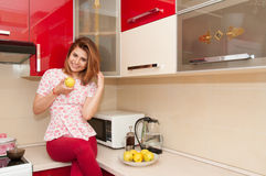 Beautiful smiling woman eating yellow apple in modern kitchen Stock Images