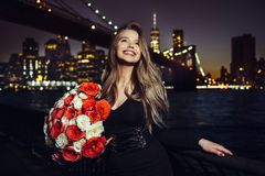 Beautiful smiling woman enjoy her birthday rose flower bouquet present at the party in the city. Royalty Free Stock Photo