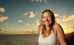 Beautiful smiling woman enjoying a tropical sunset. Beautiful tropical vacation in the warm sunny Seychelle island oceans and palm trees Royalty Free Stock Photo